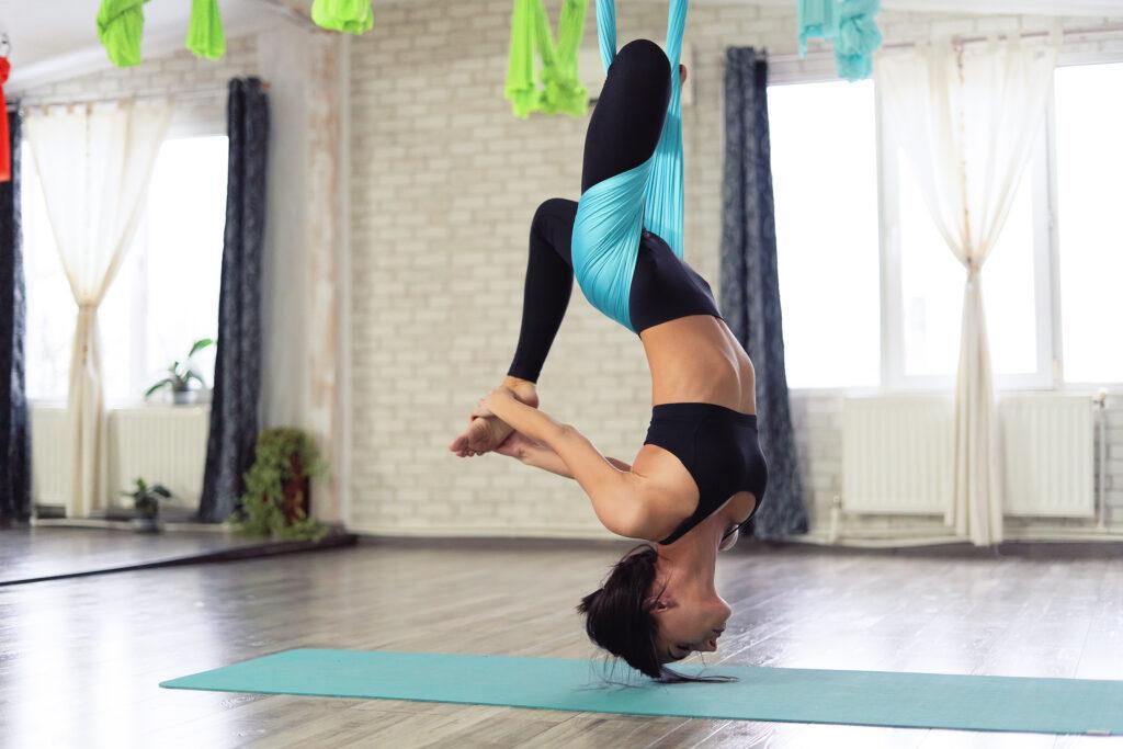 e fly yoga, une pratique tendance et ludique - Légende : Lâcher prise en découvrant de nouvelles sensations avec le fly yoga- Image libre de droits - Source : Freepick